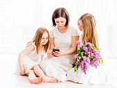Mother with daughters looking at smartphone