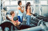 Side view of a beautiful fit woman exercising bicep curls with heavy dumbbells while sitting down ne poster