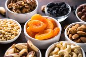 Assortment Of Nuts And Dried Fruits In Bowls. Dried Apricots, Cashew, Hazelnuts, Walnuts, Almonds, B poster