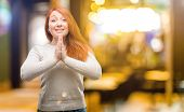 Beautiful young redhead woman with hands together in praying gesture, expressing hope and please con poster