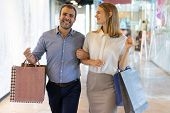 Smiling Male And Female Consumers Walking Between Shops In Mall. Joyful Couple Visiting Shopping Mal poster