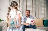 Cute Little Girl Is Giving Card Her Handsome Father And Surprising  A Gift Box At Home In The Living poster