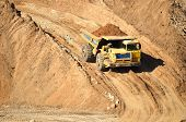 Big Yellow Dump Truck Transporting Sand In An Open-pit Mining Quarry. Mining Quarry For The Producti poster