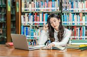 Asian Young Student In Casual Suit Thinking When Doing Homework And Using Technology Laptop In Libra poster