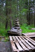 Cairn On A Wooden Platform In A Coniferous Forest On The Banks Of A Mountain River. poster