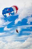 stock photo of parasailing  - Parasailing under cloudy blue sky at beach - JPG