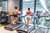 Back View Of Two Asian Adults, Shirtless Muscular Body Asian Chinese Man Running Exercising On Tread poster