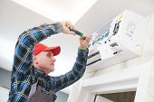 Air conditioner service. Worker at climatization system installation indoors poster