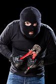 foto of wire cutter  - a burglar wearing a balaclava holding huge wire cutters over black background - JPG
