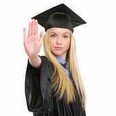 Young Woman In Graduation Gown Showing Stop Gesture