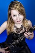 Beautiful young blonde playing electric guitar