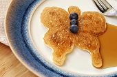 Fun butterfly shaped pancake with fresh blueberries and syrup on decorative plate.  Macro with shall
