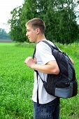 stock photo of knapsack  - teenager with knapsack in the summer field - JPG