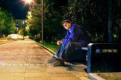 stock photo of banquette  - lonely teenager sitting in the night park alone - JPG