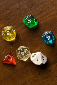 pic of dodecahedron  - Multicolored role play dice sitting on a wooden table top - JPG