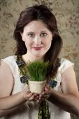 stock photo of stewardship  - Pretty woman with small pot of bright green grass - JPG