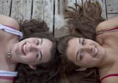 Two Teenage Girls Lying On Dock, Head To Head