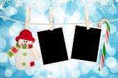 picture of clotheslines  - Blank photo frames and snowman hanging on the clothesline over blue christmas background - JPG