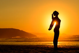 foto of breathing exercise  - Fit woman doing yoga relaxing and breathing exercises on beach at summer sunset - JPG