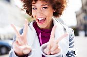 stock photo of funky  - Funky woman giving a peace sign  - JPG
