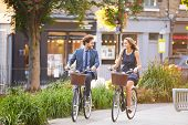 stock photo of exercise bike  - Businesswoman And Businessman Riding Bike Through City Park - JPG