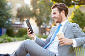 stock photo of work bench  - Businessman On Park Bench With Coffee Using Digital Tablet - JPG