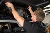 foto of car-window  - Car wrapping specialist attaching tinting foil to car window - JPG