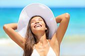 stock photo of sun-tanned  - Beach woman enjoying sun tanning on travel smiling under blue sky - JPG