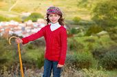 foto of shepherdess  - Kid girl shepherdess smiling with wooden baston in Spain village - JPG