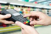 foto of terminator  - Hand with credit card swipe through terminal for sale in supermarket - JPG