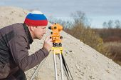image of cartographer  - Engineer at the construction site makes measurements with leveling - JPG