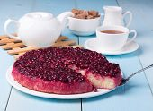 stock photo of jug  - cranberry rice pudding on blue wooden table with cup of tea sugar bowl full of brown sugar tea pot and milk jug - JPG