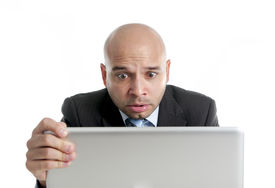 foto of spanish money  - excited desperate businessman in stress at computer laptop holding monitor watching online finances drop down or loosing money online gambling isolated on white background - JPG