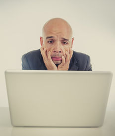 stock photo of spanish money  - excited desperate businessman in stress at computer laptop holding monitor watching online finances drop down or loosing money online gambling looking sad and distressed - JPG