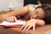 picture of fatigue  - Student tired and sleeping in her bed room over the notes while was studying - JPG