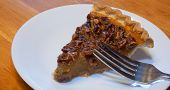 picture of pecan  - Fork above a big slice of pecan pie on a plate  - JPG