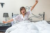 stock photo of yawn  - pretty teen girl waking up in bed yawning stretching arms