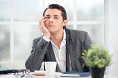 image of boring  - Young businessman is bored while working. Office interior with big window. Man looking at camera