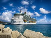 stock photo of dock  - HDR of a Cruise Ship Docked in Front of a Wall of Rocks with Blue Sky - JPG