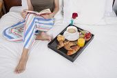stock photo of pajamas  - brunette woman green shirt striped pajama pants sitting on white bed reading red book with breakfast tray croissants orange juice strawberry kiwi cupcake red rose flower