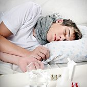 stock photo of sick  - Sick Young Man sleep on the Bed with Pills on foreground - JPG
