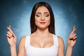 foto of fingers crossed  - Attractive young woman with eyes closed and keeping fingers crossed - JPG