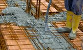 picture of concrete pouring  - Construction worker compacting liquid cement in reinforcement form work during concreting floors pouring works - JPG