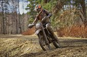 stock photo of motocross  - Motocross driver on muddy offroad track and wet terrain at cross country competition in Parola Finland - JPG