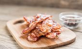 stock photo of bacon strips  - Stack Of Fried Bacon Strips On The Wooden Board - JPG
