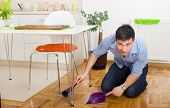 picture of broom  - Young man on knees holding broom and dustpan under table in kitchen - JPG