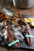 stock photo of lobster  - Raw clawed lobster on a table before cooking - JPG