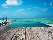 image of infinity pool  - Swimming pool and old wooden pier in the tropical hotel - JPG