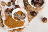 stock photo of ground nut  - Organic ground Nutmeg on white wooden cutting board - JPG