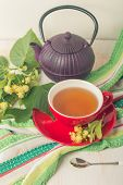 picture of teapot  - Red cup of linden tea and teapot on white wooden background - JPG